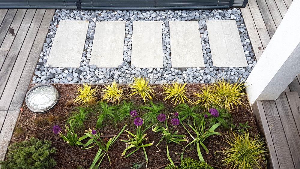 Dalle rectangulaire du jardin avec galets et végétation