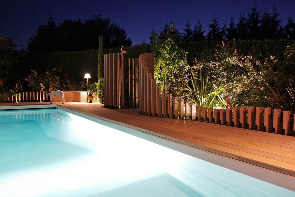 Vue de la piscine de nuit avec éclairage sur mesure
